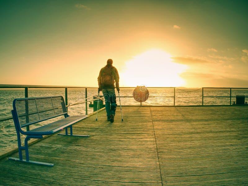 Turist på färjavågbrytare inom soluppgång eller solnedgång färger värme arkivfoton