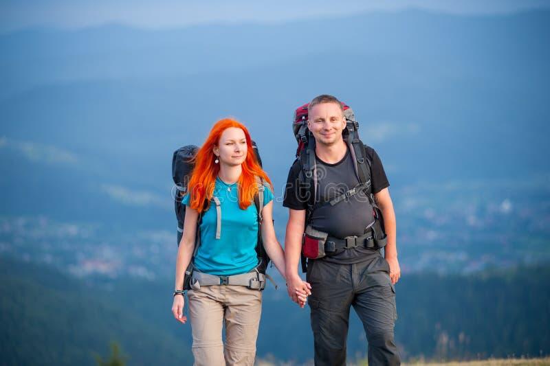 Turist- par med ryggsäckar på vägen i bergen royaltyfri bild