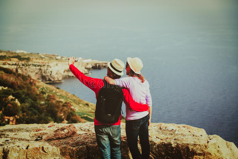 Turist- par som fotvandrar i berg som tar sefie, loppbegrepp royaltyfria bilder