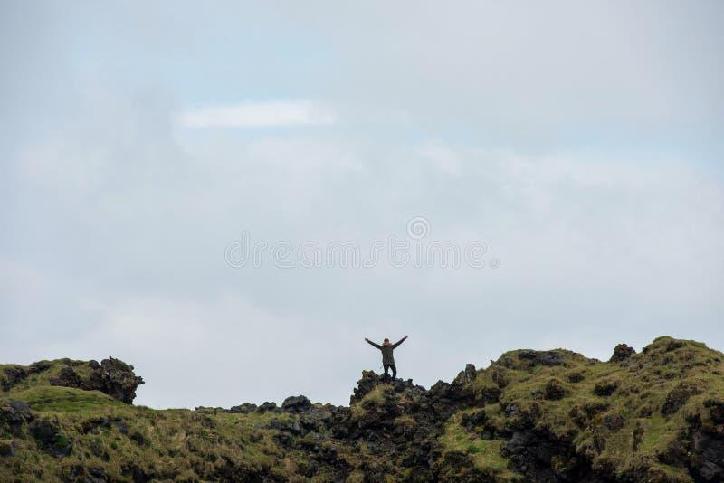 Turist- posera på den Londrangar basaltklippan, Island arkivbilder