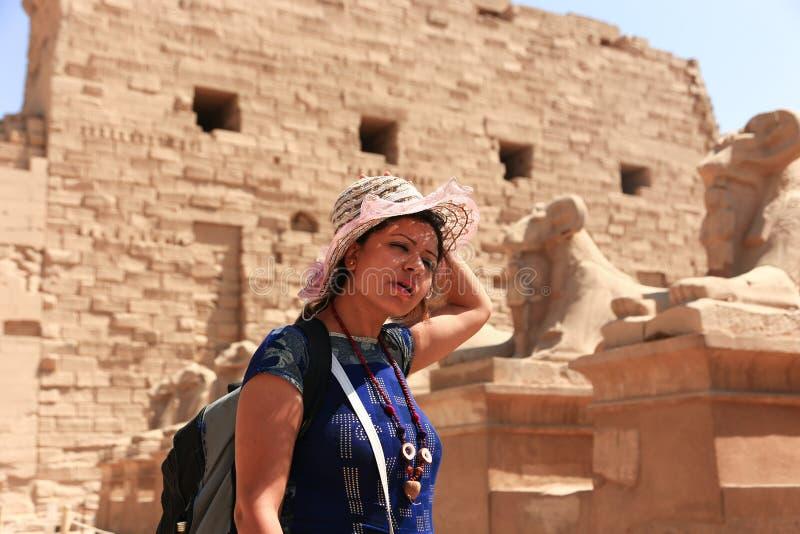 Turist- promenad för kvinna i RAM-hövdade sfinxer på den Karnak templet Luxor fotografering för bildbyråer