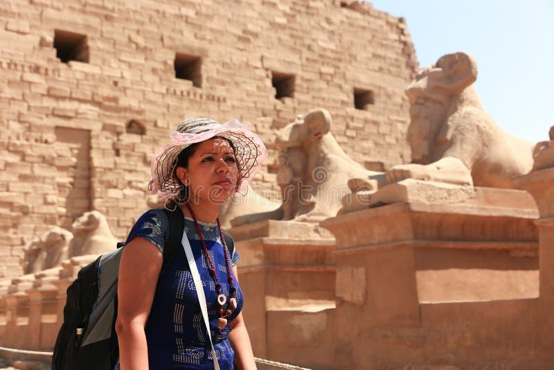 Turist- promenad för kvinna i RAM-hövdade sfinxer på den Karnak templet Luxor royaltyfria foton