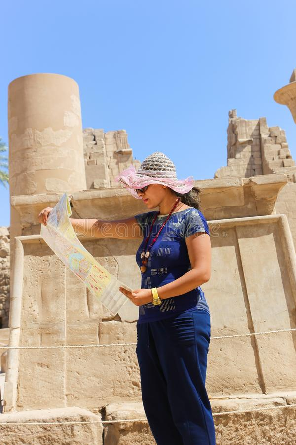 Turist- promenad för kvinna i RAM-hövdade sfinxer på den Karnak templet Luxor royaltyfri foto