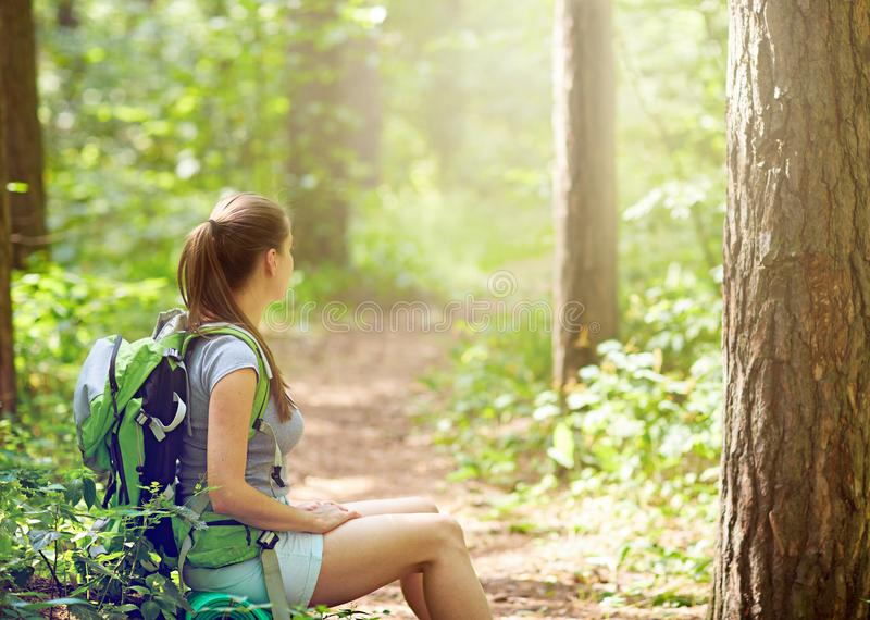Turist- sammanträde för kvinna på stopp i skog arkivfoto