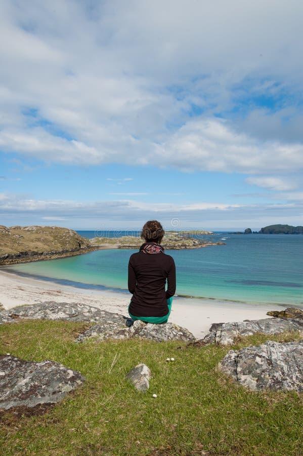 Turist- sammanträde för ung kvinna framme av en vit strand för öken arkivbilder