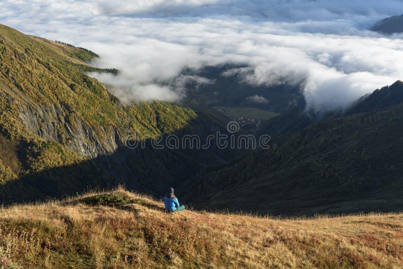 Turist- sammanträde på en kulle och blickar på bergdalen arkivfoton