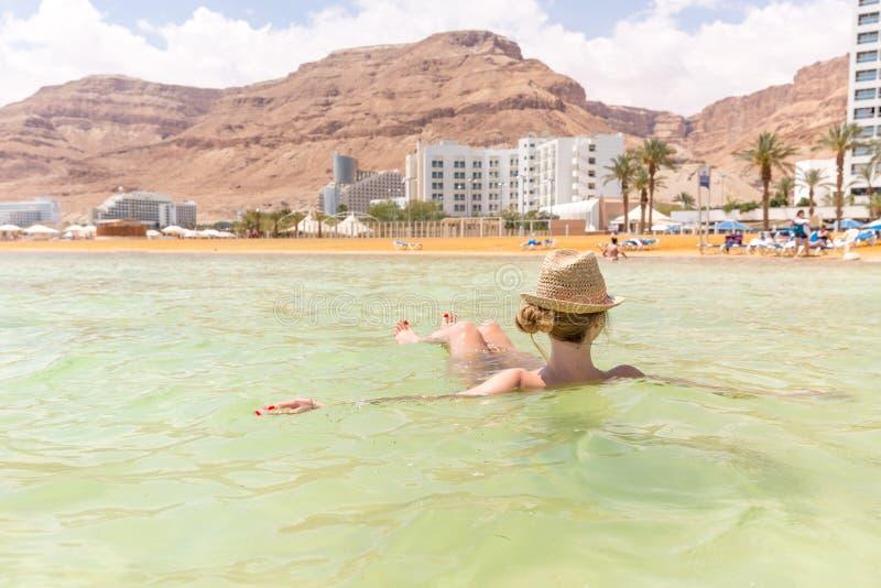 Turist- simning för ung kvinna som svävar salt vatten, dött hav royaltyfri bild
