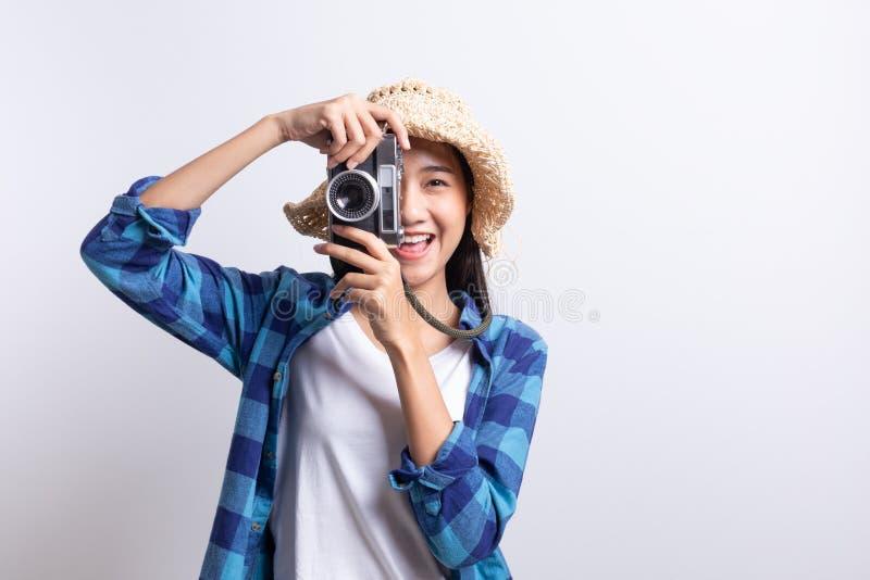 Turist som är härlig av den asiatiska kvinnan som rymmer en filmkamera och ler på vit bakgrund, skjorta för pläd för Asien flicka arkivbild