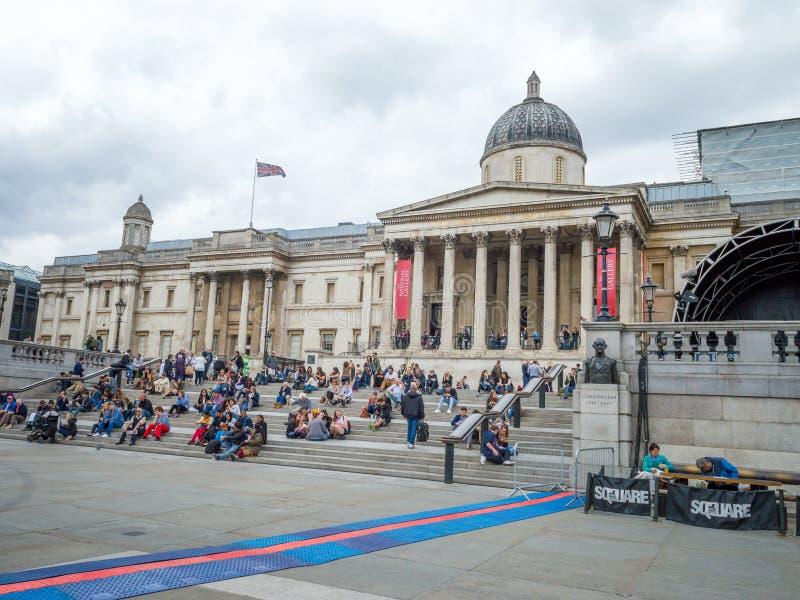 Turist som besöker National Gallery med Trafalgar Square i förgrund, London, England arkivfoto