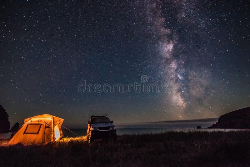 Turist som campar på havskusten på natten med den mjölkaktiga vägen royaltyfri fotografi