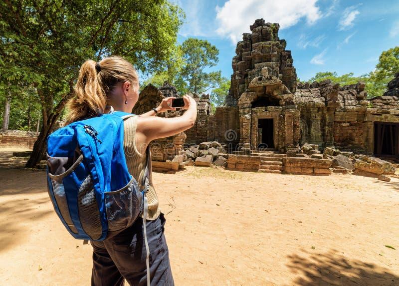 Turist som fotograferar den forntida gopuraen i Angkor, Cambodja royaltyfri foto