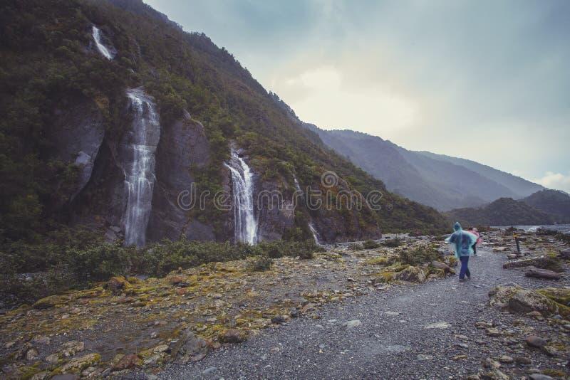 Turist som går på slinga till den franz josef glaciären i dimmigt väder royaltyfri fotografi
