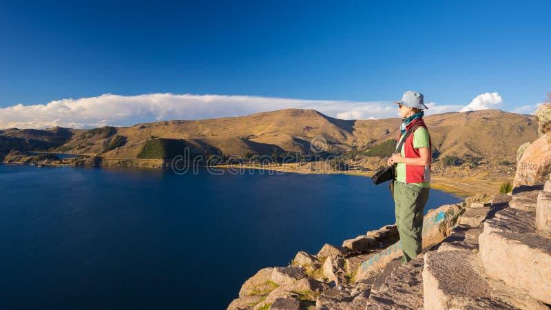 Turist som ser sikt från över, Titicaca sjö, Bolivia arkivfoto