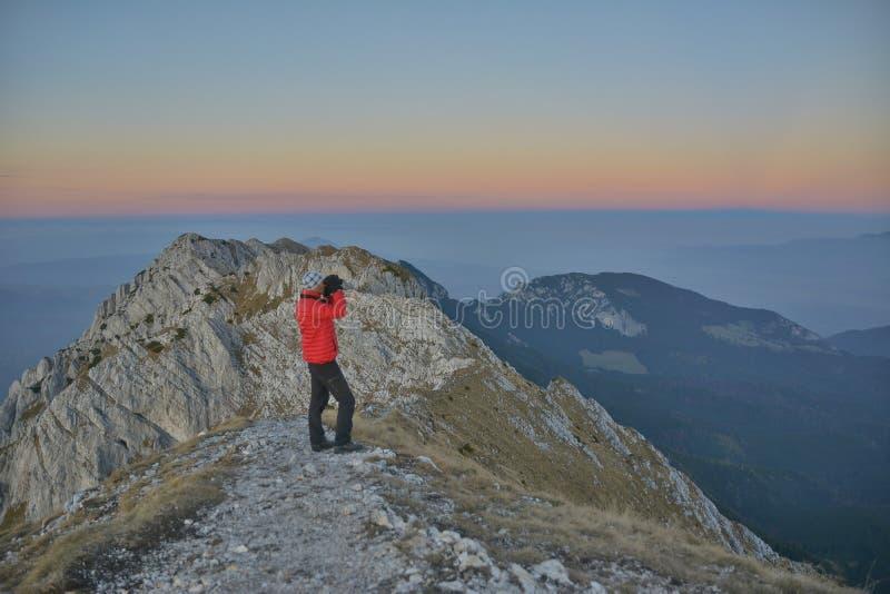 Turist som ser till och med kikaresolnedgång i bergen royaltyfria bilder