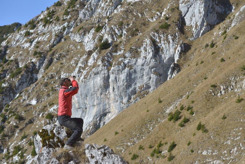 Turist som ser till och med kikaresolnedgång i bergen royaltyfri foto