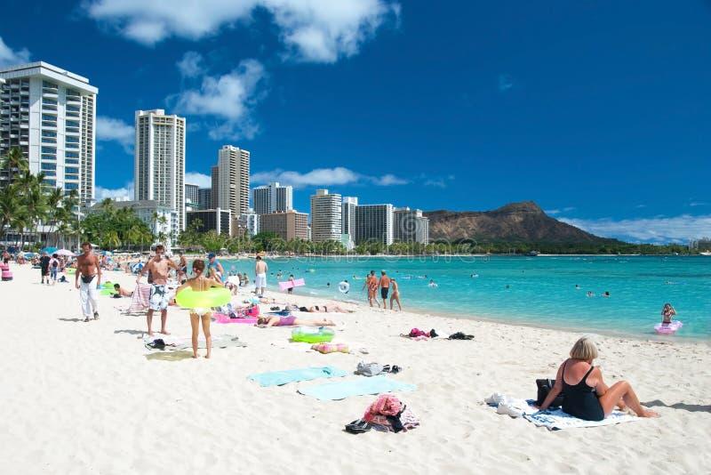 Turist som solbadar och surfar på den Waikiki stranden i Hawaii. royaltyfria bilder