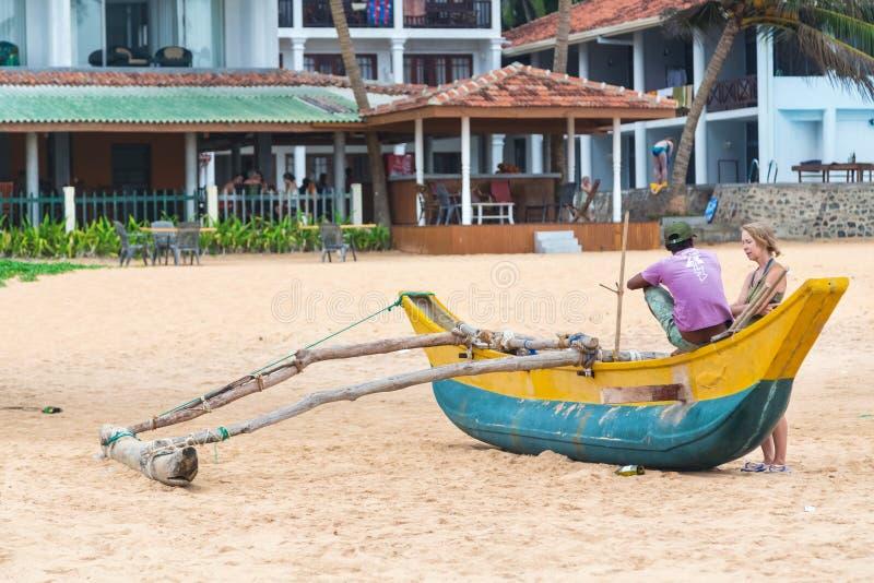 Turist som talar med lokalt mansammanträde på den traditionella srilankesiska fiskebåten arkivbild