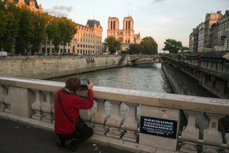 Turist som tar en bild av Notre Dame de Paris Cathedral från en bro över Seinet River på Ile de la Citera Ö royaltyfria bilder