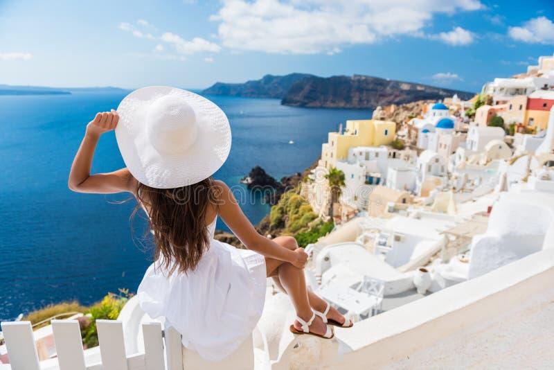 Turist som tycker om sikten av den Oia byn Santorini royaltyfri fotografi