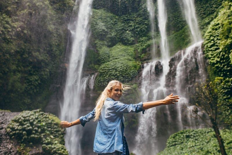 Turist som tycker om vid en vattenfall i skog royaltyfria foton