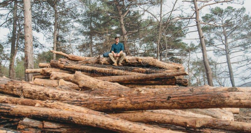 Turist som vilar på bunt av trän arkivbilder