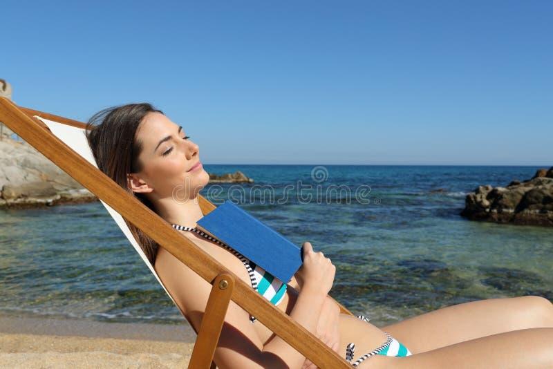 Turist- sova på stranden som rymmer en bok arkivfoto