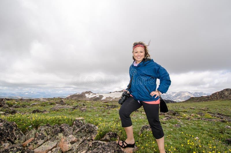 Turist- ställningar för blond kvinnlig fotograf på tundran i högt höjdområde av Montana arkivbild