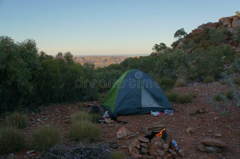 Turist- tält i läger bland äng i berget på soluppgång med campire, Australien royaltyfri bild
