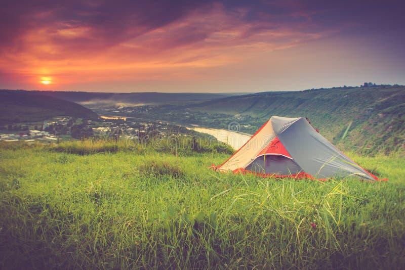 Turist- tält på grön äng på solnedgången campa för bakgrund arkivfoton