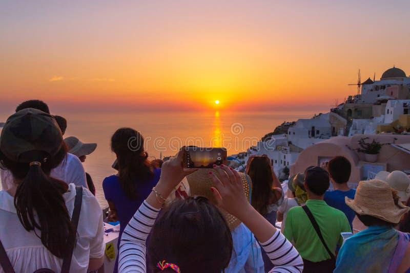Turist- tagande bild av den härliga solnedgången i Santorini, Grekland royaltyfri bild