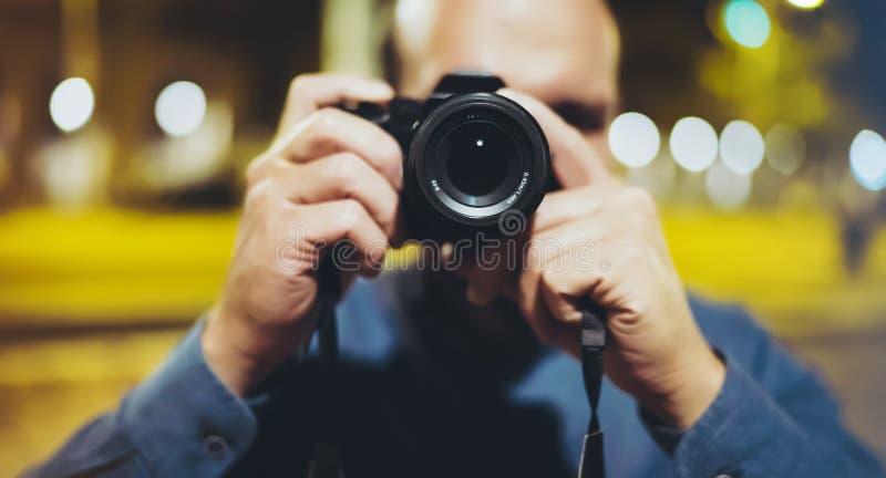 Turist- tagande foto för Hipsterfotvandrare på kamera på bakgrund av den atmosfäriska staden för afton, fotografgrabb som tycker  royaltyfri foto