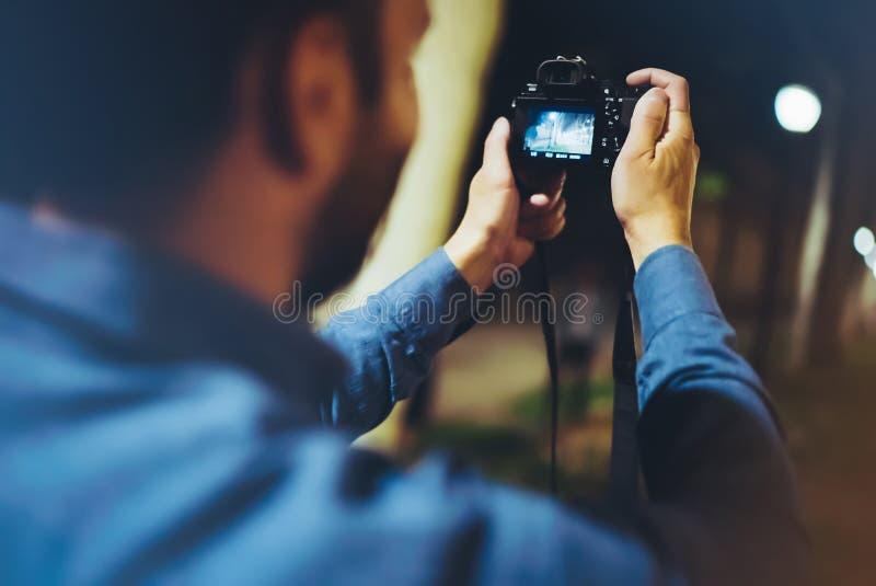 Turist- tagande foto för Hipsterfotvandrare på kamera på bakgrund av den atmosfäriska staden för afton, fotografgrabb som tycker  fotografering för bildbyråer