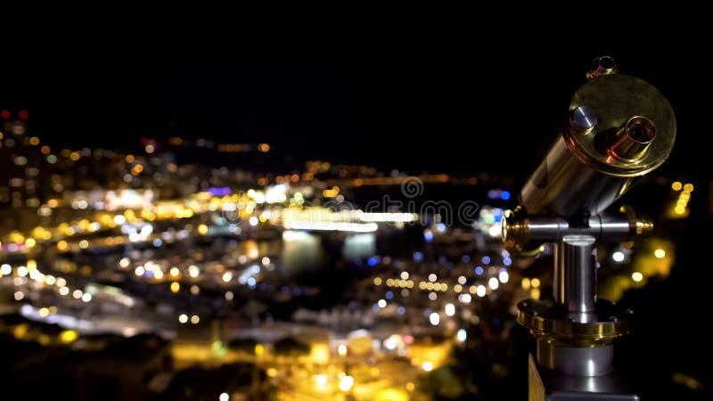 Turist- teleskop, romantisk nattsikt av den fantastiska upplysta staden på sjösidan royaltyfria bilder