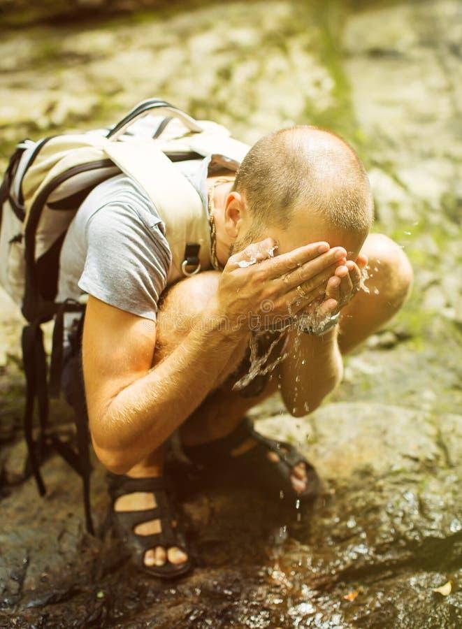 Turist- tvagningframsida i en bergflod arkivbilder