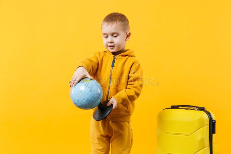 Turist- ungepojke för liten handelsresande 3-4 år gammalt som isoleras på gul orange väggbakgrundsstudio Resa för passagerare arkivbild