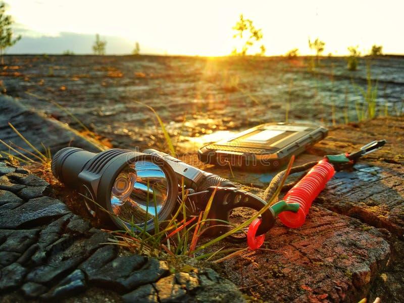 Turist- utrustning: en ficklampa, en kniv, en skyddad telefon royaltyfri fotografi