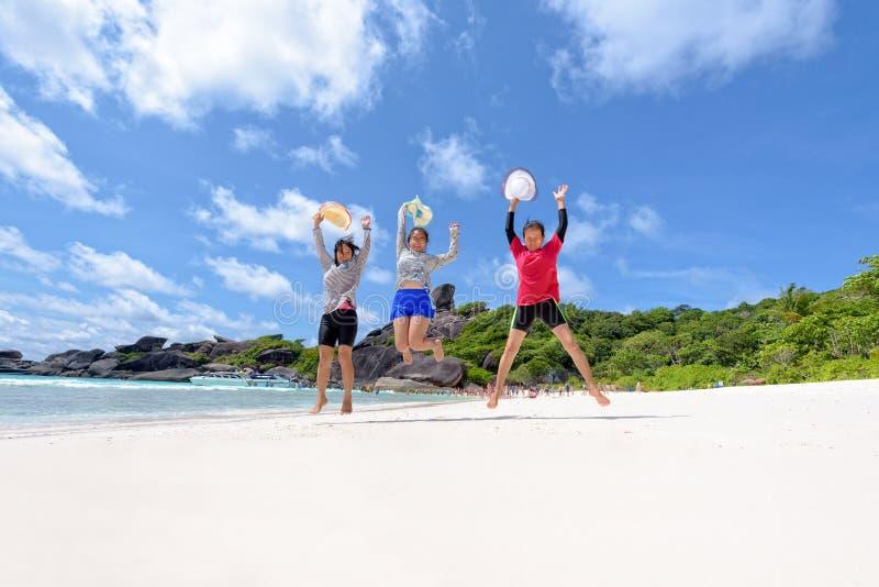 Turist- utvecklingsfamilj för kvinnor tre på stranden arkivfoto