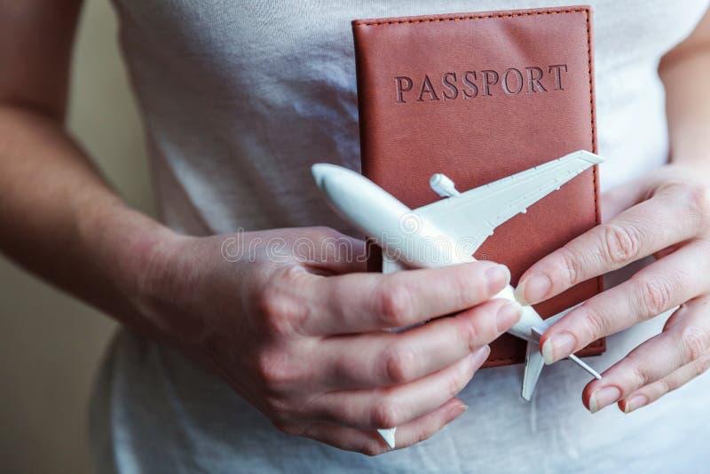 Turist- väsentlighet Kvinnliga kvinnahänder som rymmer den lilla leksakmodellnivån och passet royaltyfri foto