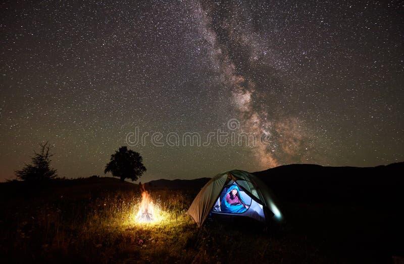 Turist- vila för kvinna på natten som campar under stjärnklar himmel och mjölkaktig väg royaltyfri bild