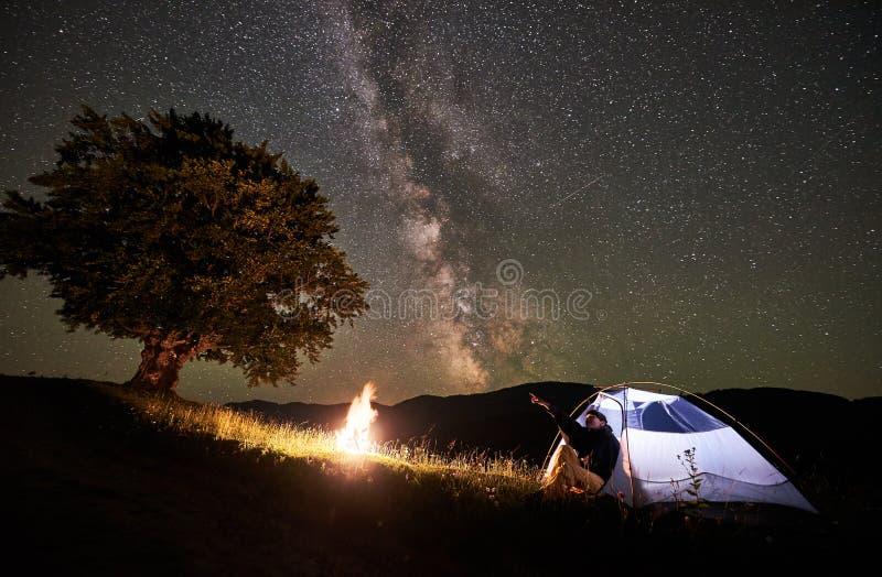 Turist- vila för kvinna på natten som campar under stjärnklar himmel och mjölkaktig väg arkivfoton