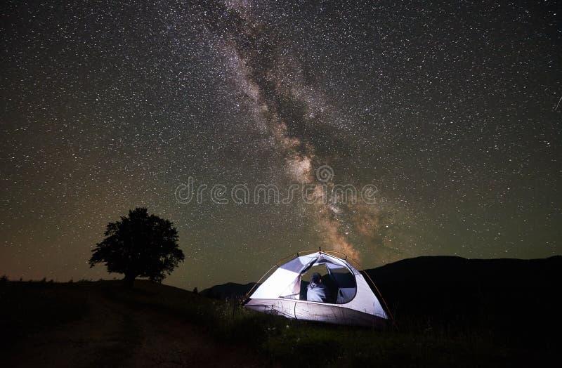 Turist- vila för kvinna på natten som campar under stjärnklar himmel och mjölkaktig väg arkivfoto
