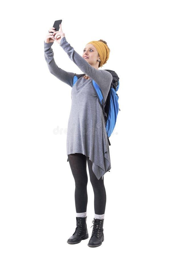 Turista à moda moderno da menina com mochila que fotografa com telefone celular fotos de stock royalty free