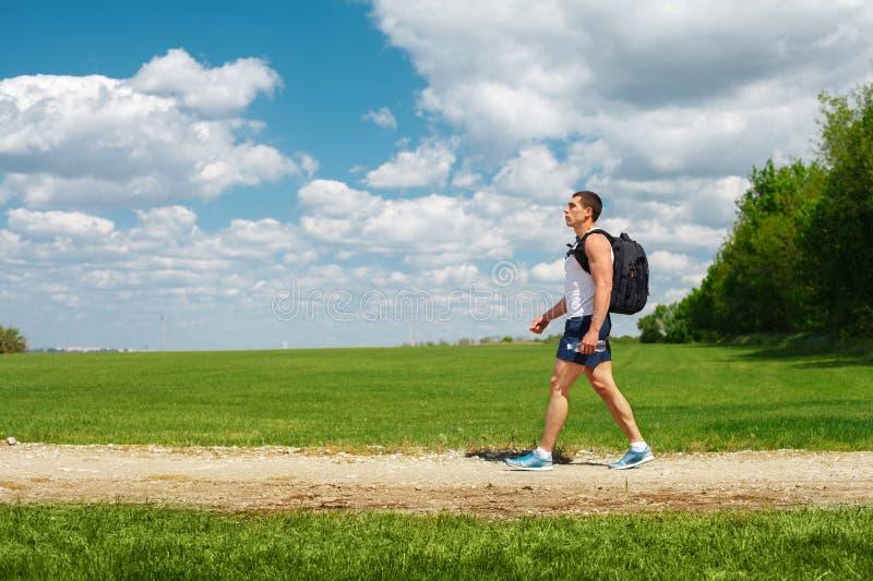 Turista activo del hombre que camina en el rastro con la mochila y la botella de agua a disposición, al aire libre fotos de archivo libres de regalías