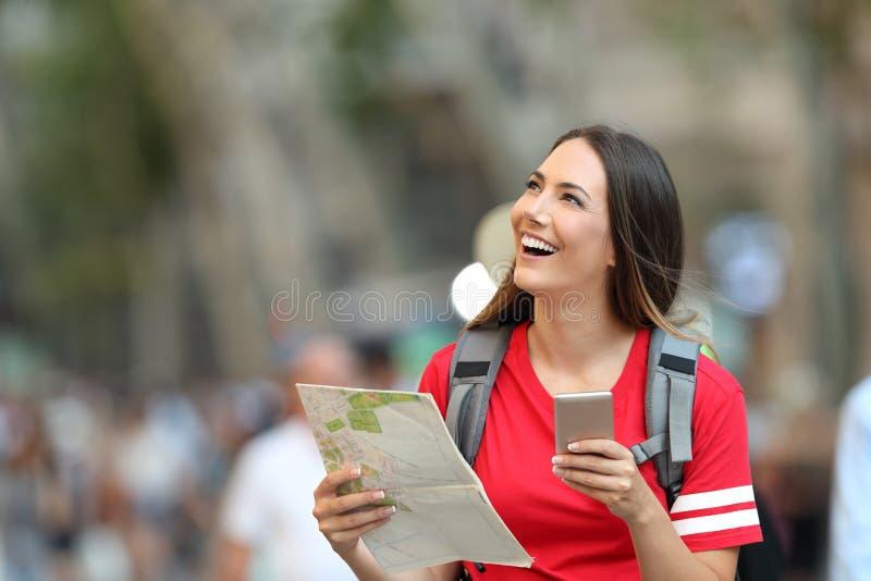 Turista adolescente que mantém o guia e o telefone que olham acima imagem de stock royalty free