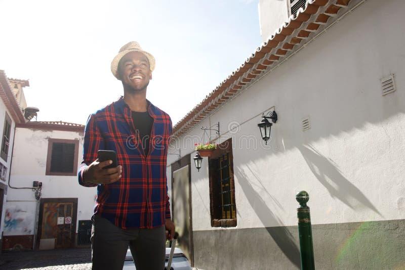 Turista afro-americano feliz que anda através da cidade com telefone celular e mala de viagem foto de stock royalty free