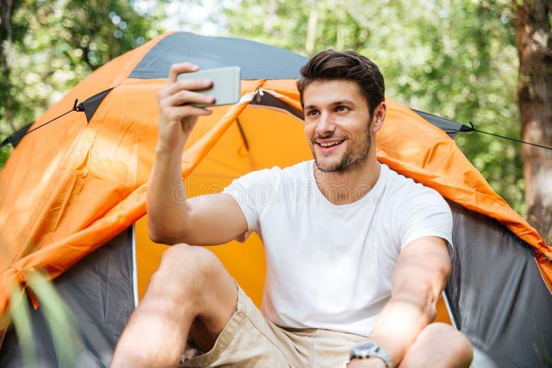 Turista alegre del hombre que toma el selfie con el teléfono móvil en bosque fotos de archivo
