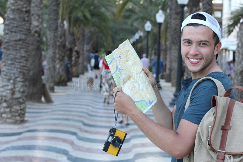 Turista alegre que guarda o mapa e a câmera durante umas férias imagem de stock