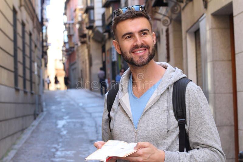 Turista alegre que guarda o mapa ou o dicionário durante umas férias imagem de stock