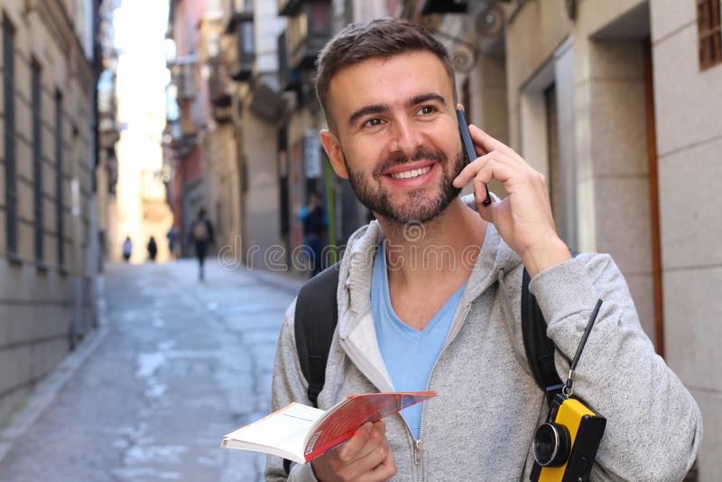 Turista alegre que guarda o mapa ou o dicionário durante umas férias e que chama pelo telefone fotografia de stock