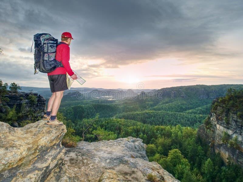 Turista alto com a trouxa grande que olha no mapa de papel Parque natural montanhoso selvagem  foto de stock royalty free